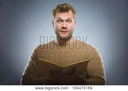 Close-up of confused man reading book against gray background.