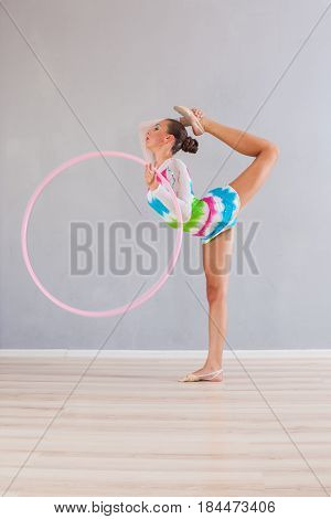 Portrait of flexible gymnast girl that doing acrobatic feat with pink hoop