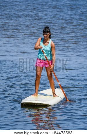 Woman stands up paddle boarding on lake. Young girl doing watersport on lake. Female tourist in swimwear during summer vacation.