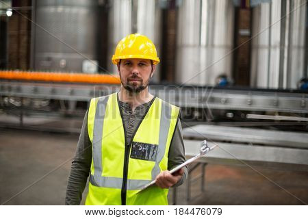 Portrait of factory worker holding clipboard in drinks production factory