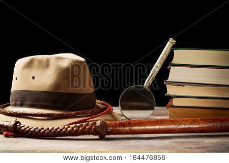 Fedora hat with bullwhip near magnifying glass and old books on black background. Adventure concept.