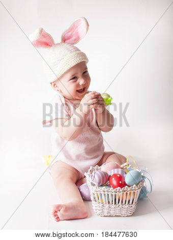 Cute baby girl sitting in a knitted rabbit hat isolated on white