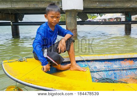 Labuan,Malaysia-April 29,2017:Portrait of a children on the fishing boat in the fisherman village at Labuan island,Malaysia.