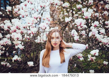 Beauty Woman Standing On Background Magnolia Blossoming Flowers, Hands On Head.