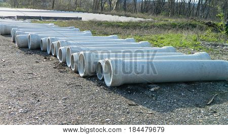Row of cement drain pipes laid out for staging