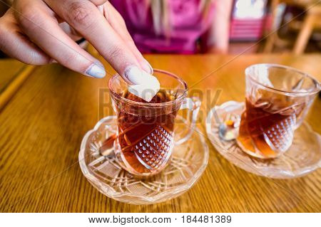 Woman's hand putting shugar to one of two tot glasses of tea at Petra, Jordan.