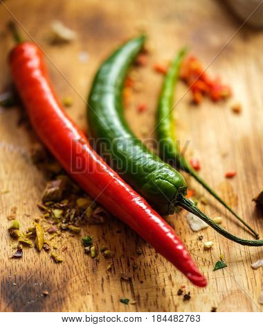 Close Up Of Red And Green Chilli Peppers On Wooden Cutting Board.