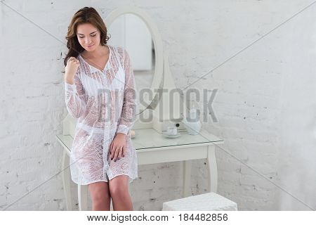 The tender image of a young girl in the morning in a bright room in lingerie.