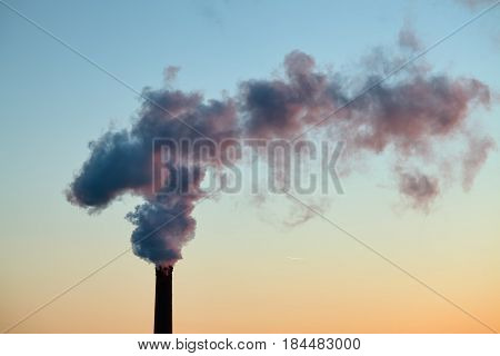 close-up factory brick chimney. The smoke from the pipe cogeneration plant. Steam escaping from a trumpet on the sky background in the sunlight. Ambient air pollution industrial emissions
