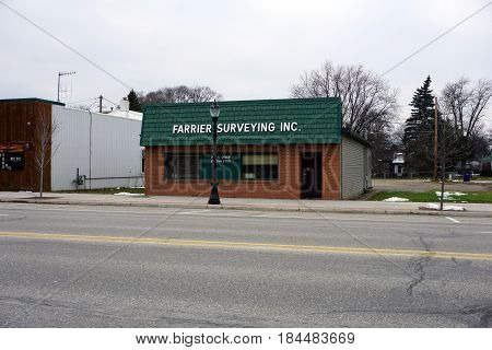 KALKASKA, MICHIGAN / UNITED STATES - NOVEMBER 27, 2016: Farrier Surveying Inc., in downtown Kalkaska, offers land surveying, and oil and gas staking services.