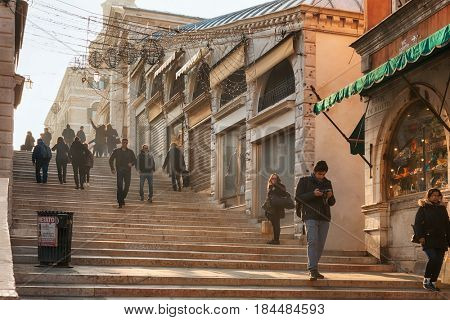 VENICE, ITALY - February 18, 2017 People walking in the morning after crossing the famous Ponte Rialto Bridge in Venice, Italy
