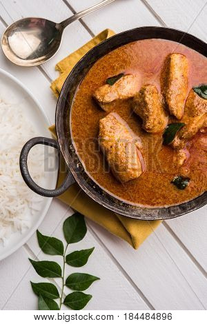 tasty fish curry served with white cooked basmati rice with curry leaves in the background, favourite coastal indian food