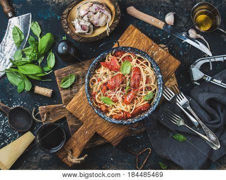 Italian style pasta dinner. Spaghetti with tomato and basil in plate on wooden board and ingredients for cooking pasta over dark plywood background, top view