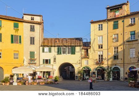 Little shops around one of the four gateways of Piazza dell' Anfiteatro, the public square of Lucca, Tuscany, Italy - 29 September 2011
