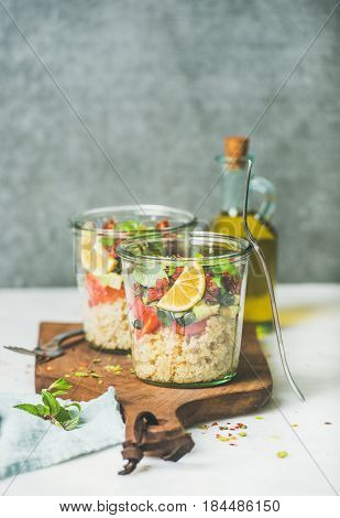 Healthy vegan energy boosting salad with quionoa, avocado, dried tomatoes, basil, olive oil, mint in glass jars, marble background, selective focus, copy space. Clean eating, vegan, detox food concept