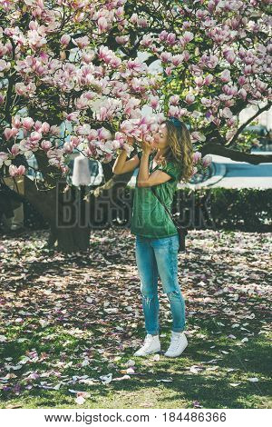Young woman in casual clothes smelling magnolia flowers under magnolia tree