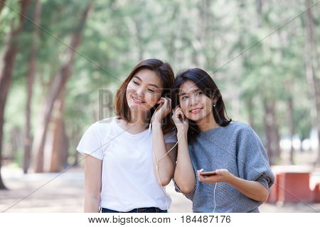 Happy girlfriends listen to music whit her friend in the park