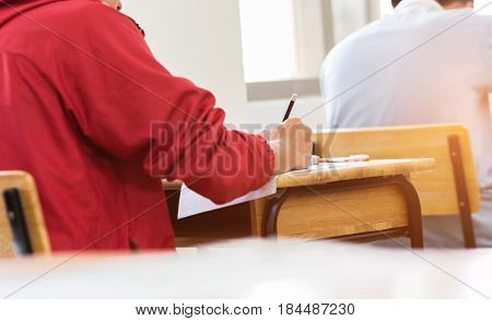 young man taking exam test choice with pencil college student preparing note for the exam at school classroom.