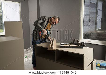 Carpenter Using Cordless Screwdriver