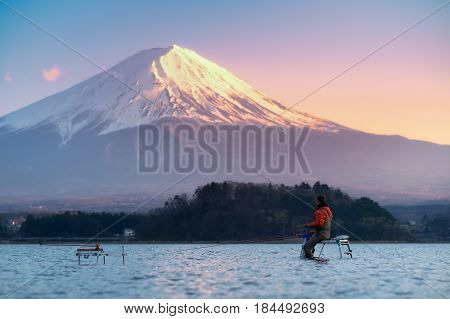 Fisherman In Kawaguchiko Lake With Fuji Mountain