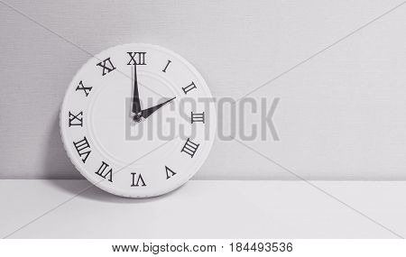 Closeup white clock for decorate in 2 o'clock on white wood desk and wallpaper textured background in black and white tone with copy space