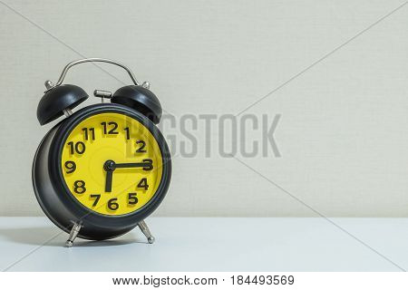 Closeup yellow and black alarm clock for decorate show a quarter past six or 6:15 a.m.on white wood desk and cream wallpaper textured background tone with copy space