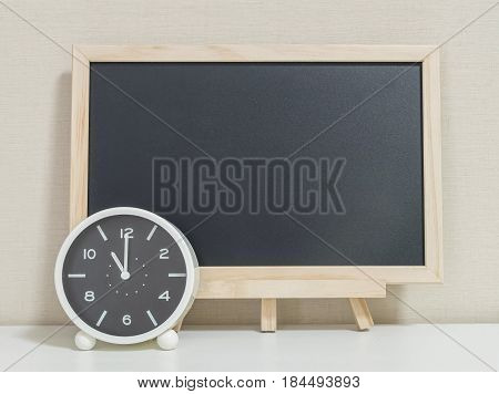 Closeup alarm clock for decorate show 11 o'clock with wood black board on white wood desk and cream wallpaper textured background selective focus at the clock