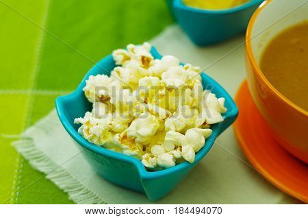 Delicious popcorn inside of a magenta bowl.
