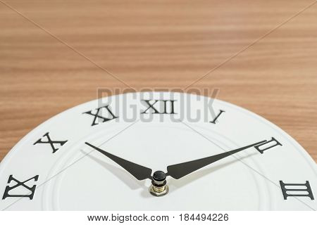 Closeup part of white clock for decorate in ten past ten o'clock on wood desk textured background with copy space