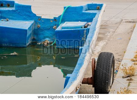 Small blue fishing boat missing engine on trailer full of water with a green hose at aft to drain water.