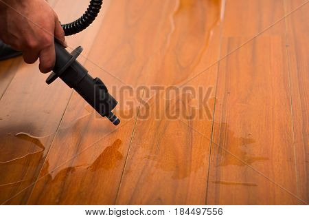 cleaning water on the wood floor with vacuum cleaner.