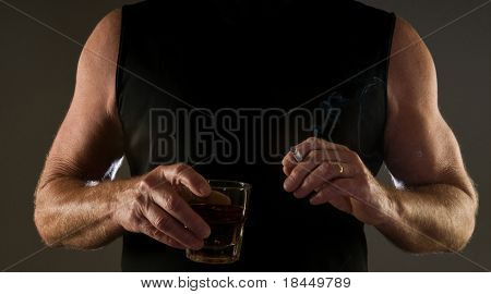 fit, muscular man drinking and smoking