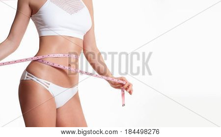 Diet concept woman measuring her waist with a measure tape poster