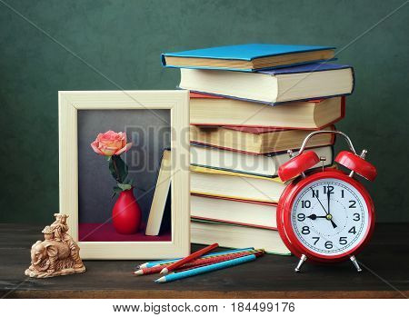 Pile of books red alarm clock frame colored pencils and the girl's figure on an elephant on a wooden table. A still life with books.