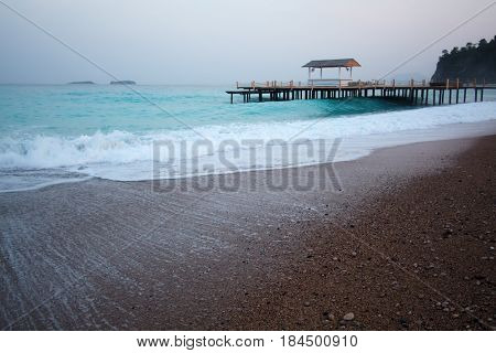 Summer arbor on beach. Breathtaking view on mediterranean sea. White wooden pier on evening time