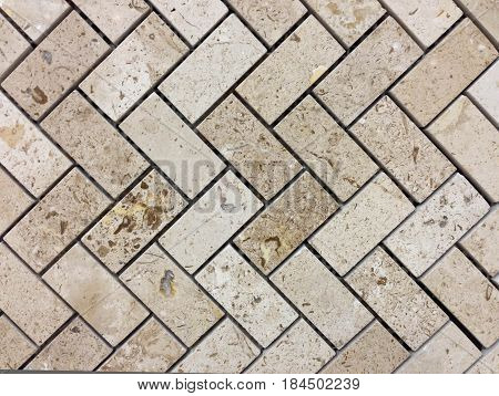 Beige or light brown colors Stone wall texture.Wall pattern or abstract background. Herringbone pattern.
