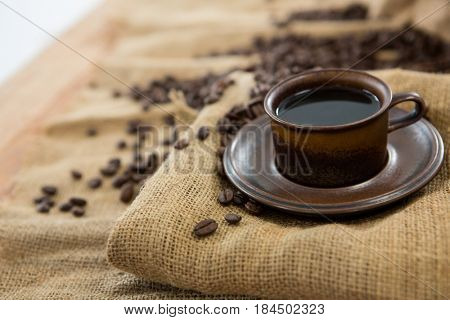 Black coffee served on sack with coffee beans on sack textile