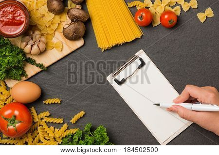 Italian spaghetti photo recipe. Hand with pen writting on blank paper on the kitchen table surrounded with products.