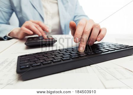 Financial accounting. Business woman using calculator and computer keyboard