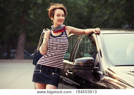 Happy young woman with handbag next to her car. Stylish fashion model in tank top with pixie hairstyle outdoor