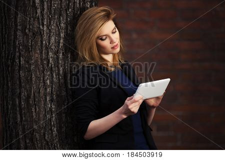 Young blond business woman using tablet computer in city street. Stylish fashion model in black jacket outdoor