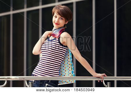 Happy young woman with shopping bag next to mall . Stylish fashion model in tank top with pixie hairstyle