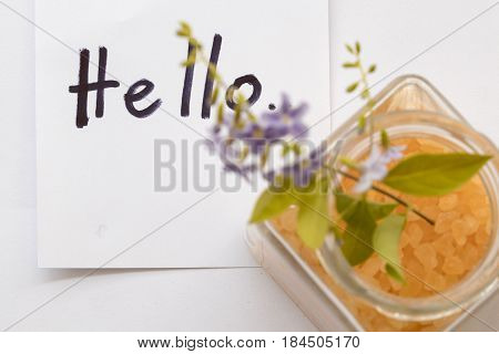 hello greeting message card and spa salt aroma of all flowers skin food with purple flowers on background white