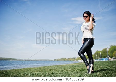 Brunette Girl On Women's Leather Pants And White Blouse, Sunglasses, Posed On Geen Grass Against Bea