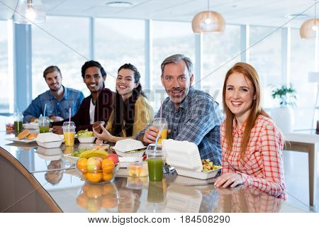 Portrait of creative business team having meal in office