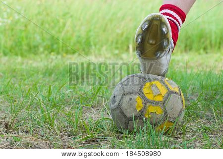 Soccer on old and bad field with shabby ball closeup.