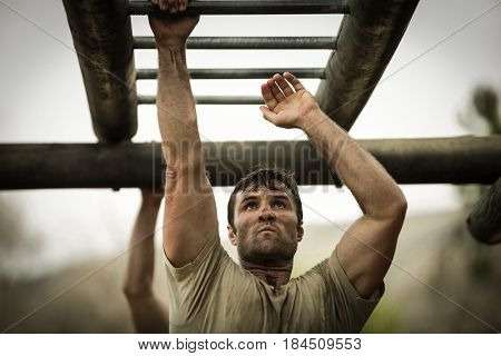 Soldier climbing monkey bars in boot camp
