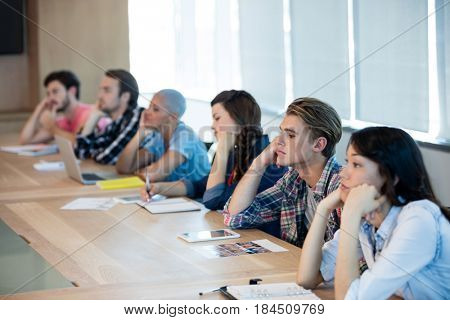 Bored creative business team attending a meeting in conference room