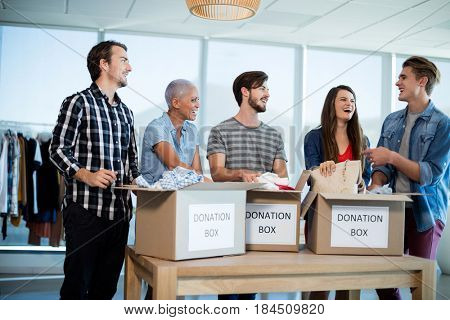 Happy creative business team sorting clothes in donation box in office
