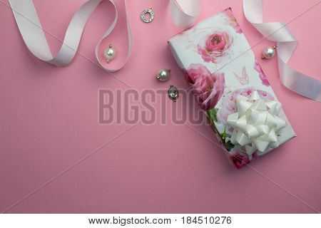 Pink background with wrapped gift white satin ribbon and pearl and crystal charms for Mothersday